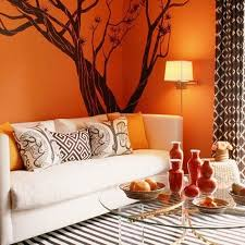 Living room design with orange wall paint, white sofa, black tree wall  sticker and decor accessories in orange color