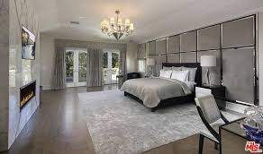 huge master bedroom with chandelier and fireplace