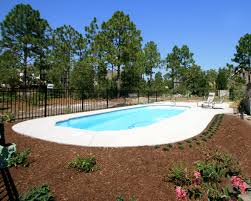 by raising the pool a little to meet the grade on the upslope of the yard and building a sloping berm on the opposite side a retaining wall will become