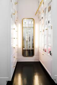 white custom closet with curved gold wall mirror