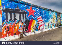 panoramic view of famous berlin wall decorated with colorful graffiti street art at historic east side gallery on a moody cloudy day in summer berlin on famous berlin wall graffiti artist with panoramic view of famous berlin wall decorated with colorful