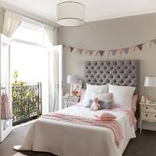 Pink and gray girl's room features walls painted a warm gray lined with a  pink and