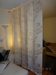 ikea panel curtains hung on a wire curtain rod divider between bedroom and