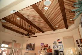 tray ceiling adorned with wood ceiling planks and fake timber beams