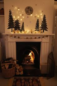 hearth mantel: evergreen trees, moon, ceramic house lanterns, string  lights, garland  Christmas Fireplace ...