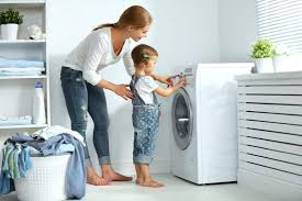 mother and daughter using a washing macine