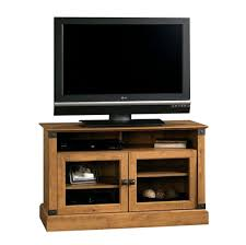 small wooden tv stand featuring double glass door with metal knob and 2 tier shelves inside plus center upper open storage compartment