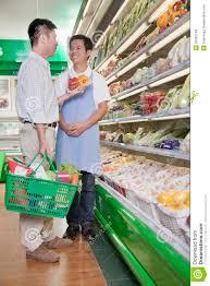 s clerk assisting man in supermarket beijing royalty s clerk assisting man in supermarket beijing