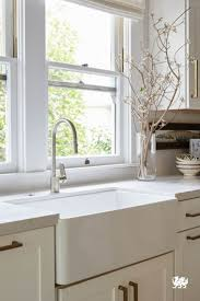 A beautiful white farmhouse sink takes center stage in this monochromatic  kitchen. Large windows,