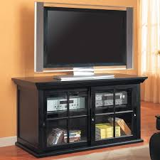 black stained wood tv stand and media storage unit with glass door placed on