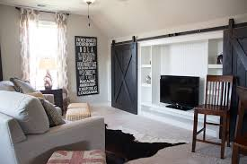 ingenious use of barn doors to hide the living room entertainment center design signature