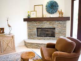 interior grey stone fireplace with brown wooden mantel shelf and white hearth added by brown