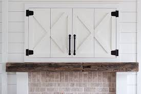 barn door tv cabinet above fireplace the tv is concealed in the custom farmhouse inspired
