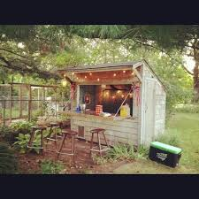 this is a great small rustic bar shed complete with fun lights and bar stools