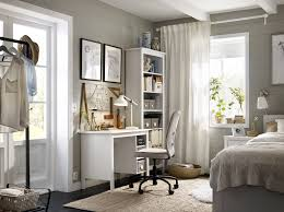 a corner in the bedroom with a white desk and a high bookcase completed with
