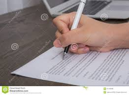 close up of hand completing an employment application stock photo close up of hand completing an employment application