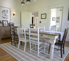 dining room wonderful crystal chandelier slopped wood leg walnut legs sunken wine storage concrete tile floor white chairs dark table with rustic country