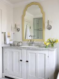 This Traditional White Bathroom Features A Gold Trim Mirror - Yellow and white bathroom