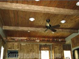 Wood ceiling planks conjoined with faux ceiling beams to create a charming,  rustic ceiling design