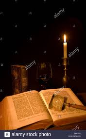 old open book a magnifying gl a gl of red wine and a candle