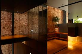 fashionable modern interior home decor with natural exposed brick wall as well as laminate wood floor feat custom l shape open rack design added glass