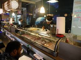 san diego minimum wage increase debate restaurant owners hesitate restaurant chef prepares meal for guest at sushi bar while server grabs plates for his table
