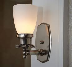 this bathroom wall sconce features an elegant cast mounting plate and decorative cast flower