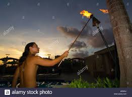 lighting tiki torches. hawaiian man lighting tiki torches waikiki honolulu hawaii usa stock photo