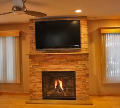 furniture exclusive black lcd television over black gas fireplace with stone surround and wood mantel