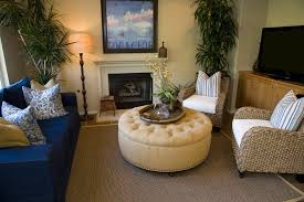 When To Use A Round Coffee Table. Cozy living room centers round button  tufted and nail head trimmed ottoman between twin wicker armchairs