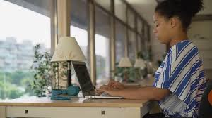 big beautiful modern office photo. subscription library professional woman works near big panoramic office mixed race female typing on the laptop sitting beautiful modern photo