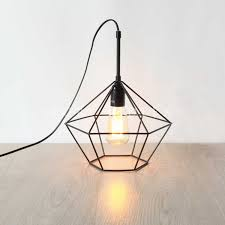 wire cage pendant light. Black Diamond Cage Pendant Sitting On A Wooden Floor With The Light Wire N