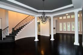 formal dining rooms with columns. in this raleigh luxury home: the formal dining room is open to two story living room, separated by interior white columns. a curved staircase flows rooms with columns l