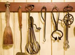 antique kitchen utensils hanging from hooks