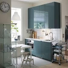 A Small Modern Kitchen With White Walls And High Gloss Gray