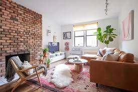 exposed brick living room with pink rug and tan leather sofa