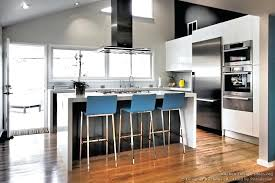 glamorous blue bar stools provide a pop of color in this monochromatic kitchen cabinets modern two tone black white vaulted ceiling island wood floor for