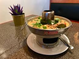 the large serving of tom kha soup with tofu garnished with cilantro and galangal root