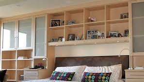 surround head of bed with built in shelves and cabinets