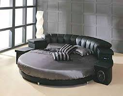 Many people choose to make their round bed into a home entertainment  center. This one