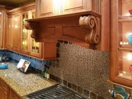 a few well placed corbels can make the transition seamless creating visual flow from the sharp angles of cabinet corners down or up to the next cabinet