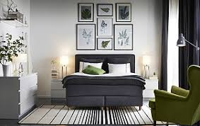 A bedroom furnished with a dark grey divan bed combined with white chest of  drawers and