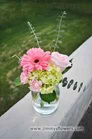 Pink and green flowers in a clear glass jar. (Garden rose, gerbera daisy