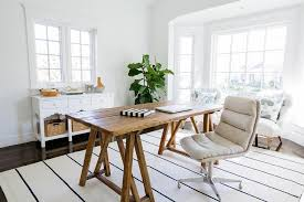 chic home office features a rustic wood sawhorse desk paired with an oatmeal linen rolling task chair placed atop a white rug with dark blue thin stripes chic home office features