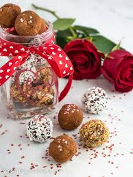 homemade chocolate truffles in a jar with a red ribbon and white hearts for a valentine