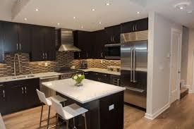 dark kitchen cabinets with light floors under rectangular flush mount ceiling light marble two tiered island countertop laminate butcherblock island