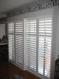 interior horizontal blind sliding glass door on the white wall plus brown wooden flooring