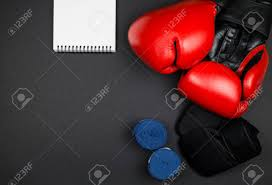 pairs of red leather boxing gloves and blue hand wraps inner gloves opened notepad