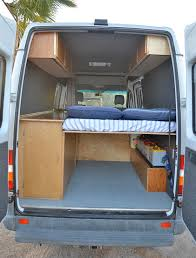 diy sprinter camper van interior showing high rear bed and house battery bank photo