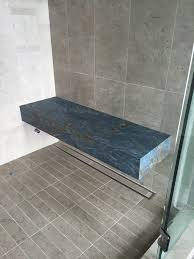 custom shower with a floating bench seat made of rare blue azul